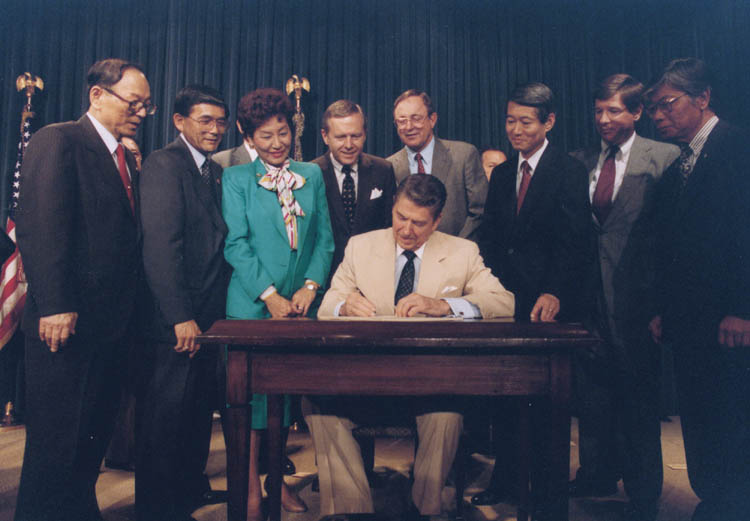Ronald_Reagan_signing_Japanese_reparations_bill
